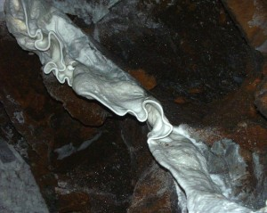 A curtain-like formation - the result of calcium carbonate-rich water running along the ceiling of the Sterkfontein Quarry Cave. It would probably have taken millennia to form a curtain of this size!